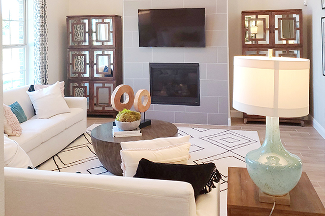 nicely staged living room with a white sectional and a fireplace