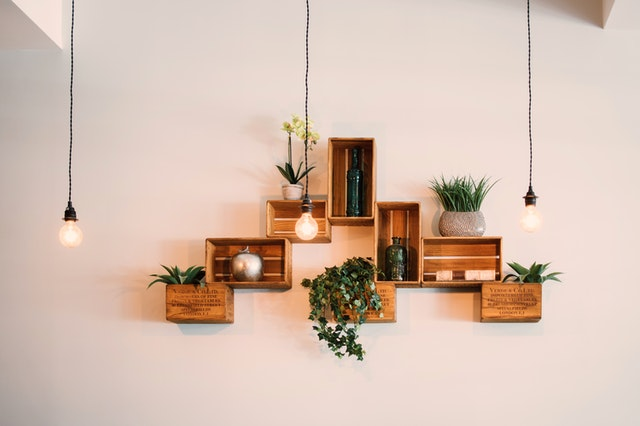 three lightbulbs hanging from the ceiling in front of floating shelves made from wood