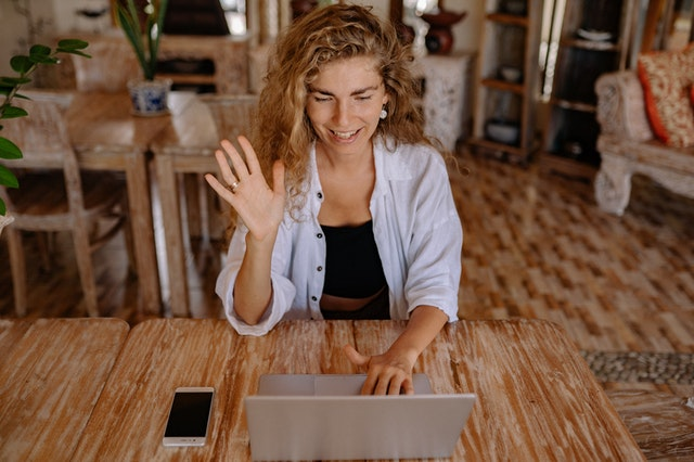 woman seated, smiling and waving at her laptop webcam